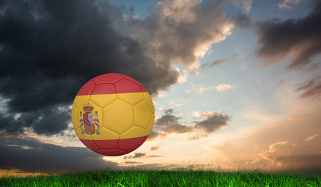 Football in spain colours against green grass under blue and orange sky photo