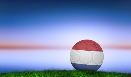 Football in holland colours against green grass under blue and purple sky photo