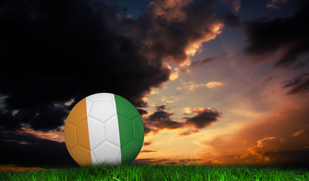 Football in ivory Coast colours against green grass under dark blue and orange sky photo