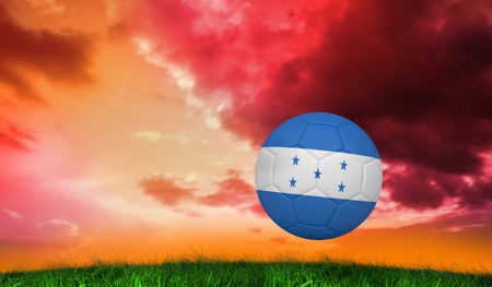 Football in honduras colours  against green grass under red and purple sky photo