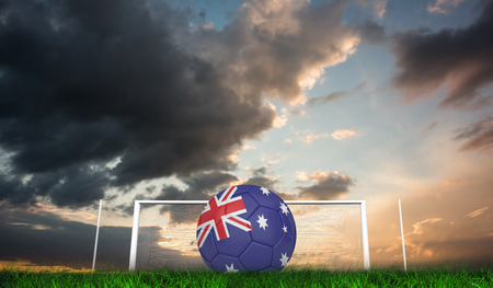 Football in australia colours against green grass under blue and orange sky photo