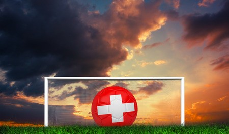 Football in swiss colours against green grass under dark blue and orange sky photo