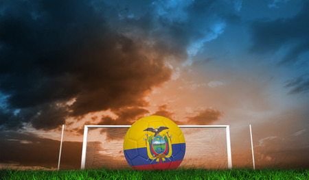 Football in ecuador colours against green grass under blue and orange sky photo