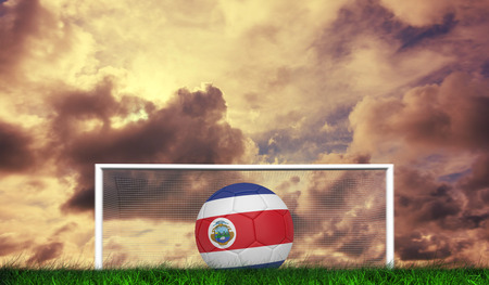 Football in costa rica colours against green grass under cloudy sky photo