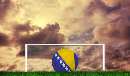 Football in bosnia and herzegovina colours  against green grass under cloudy sky photo