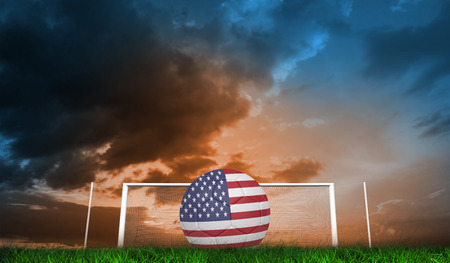 Football in america colours  against green grass under blue and orange sky photo