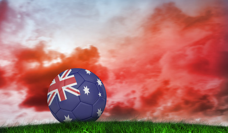 Football in australia colours against green grass under red cloudy sky photo