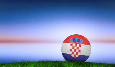 Football in croatia colours against green grass under blue and purple sky photo