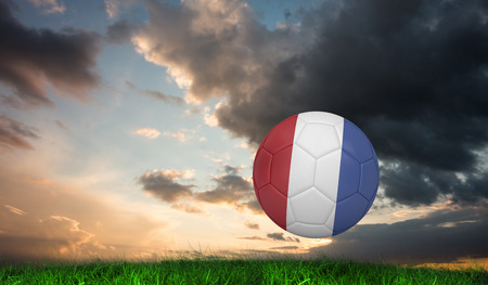 Football in france colours against green grass under blue and orange sky photo