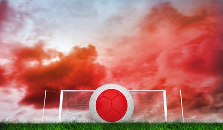 Football in japan colours against green grass under red cloudy sky photo