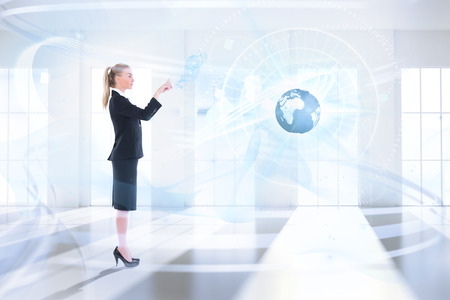 Businesswoman pointing against bright room with windows photo