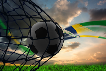 Composite image of football in back of the net  against brazilian flag flow Stock Photo