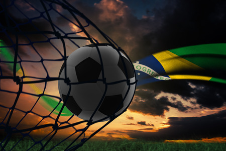 Composite image of football in back of the net against brazilian flag flow photo