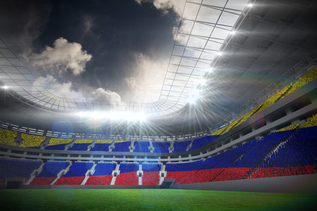 Digitally generated colombia national flag against football stadium with fans in white photo