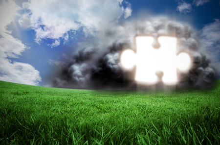 Composite image of jigsaw in cloud against green field under blue sky photo