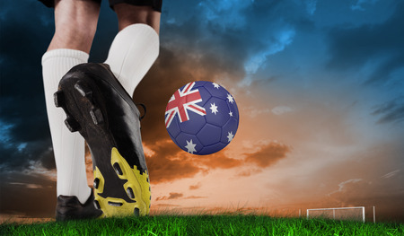 Composite image of football boot kicking australia ball against green grass under blue and orange sky photo