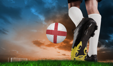 Composite image of football boot kicking england ball against green grass under blue and orange sky photo