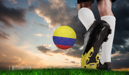 Composite image of football boot kicking colombia ball against green grass under blue and orange sky