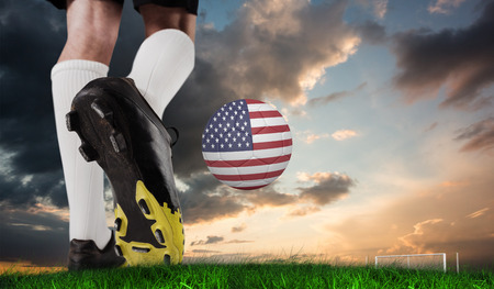 Football boots against green grass under blue and orange sky photo