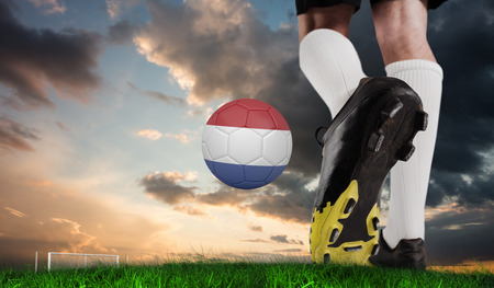 Composite image of football boot kicking dutch ball against green grass under blue and orange sky photo