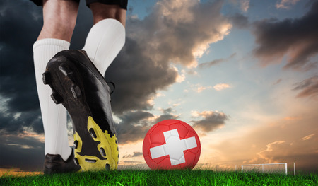 Composite image of football boot kicking swiss ball against green grass under blue and orange sky photo