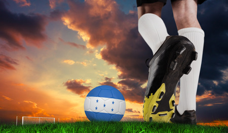 Composite image of football boot kicking honduras ball  against green grass under dark blue and orange sky photo