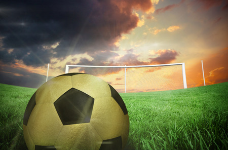 Gold football against football pitch under cloudy orange sky photo
