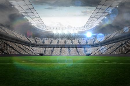 Grote voetbalstadion met verlichting onder bewolkte hemel