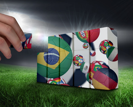 Hand building wall against football pitch under bright lights photo