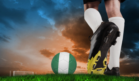Composite image of football boot kicking nigeria ball  against green grass under blue and orange sky photo