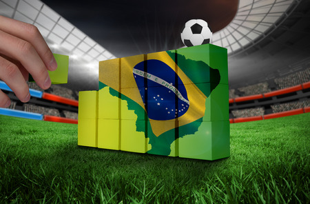 Hand building wall of green brazil outline with flag photo