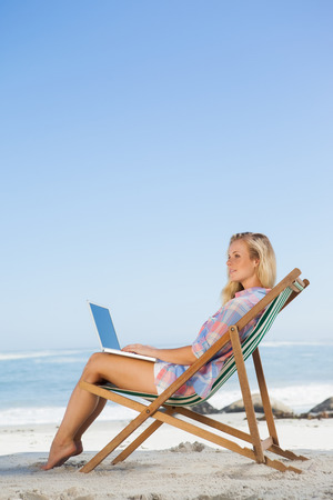Pretty blonde sitting on beach using her laptop on a sunny day photo