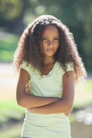 Young girl frowning with arms crossed in the park on a sunny day photo