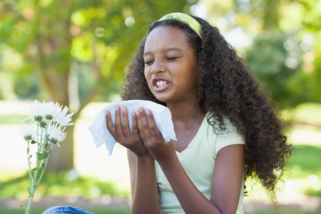Young girl sitting by flower and sneezing in the park on a sunny day photo