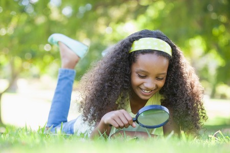 Young girl looking at grass through magnifying glass in the park on a sunny day Stock Photo - 29045813