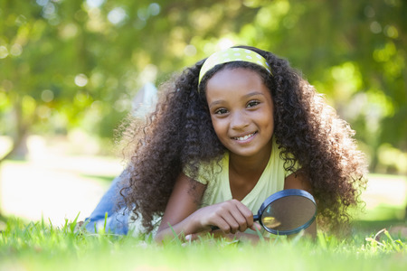 Young girl holding magnifying glass in the park smiling at camera on a sunny day Stock Photo - 29051451