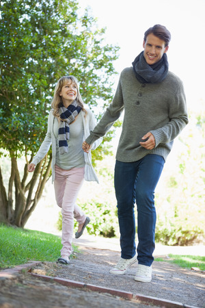 Cute couple walking hand in hand in the park on a sunny day photo