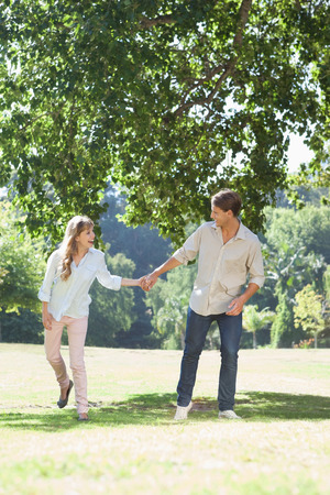Carefree couple standing in the park holding hands on a sunny day photo