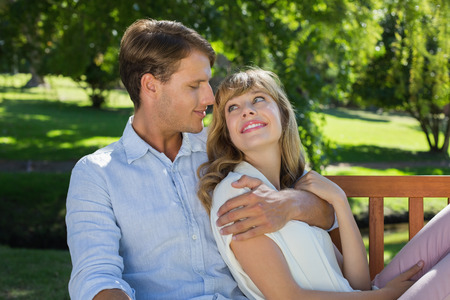 Affectionate couple relaxing on park bench together smiling at each other on a sunny day photo