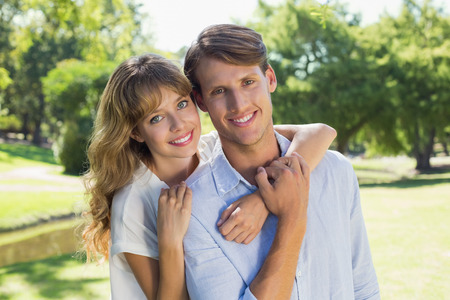 Cute couple smiling at camera together in the park on a sunny day photo
