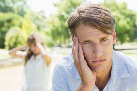 Upset man looking at camera after a fight with his girlfriend in the park on a sunny day