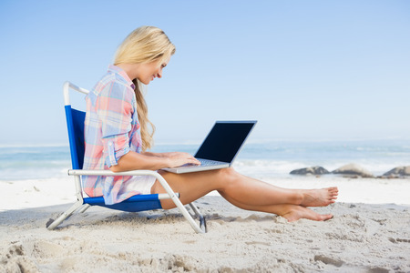 Woman sitting on beach using her laptop on a sunny day photo