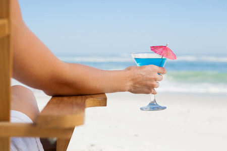 Woman sitting in deck chair with a cocktail at the beach on a sunny day photo