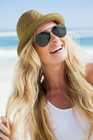 wavy hair: Stylish blonde smiling on the beach on a sunny day Stock Photo