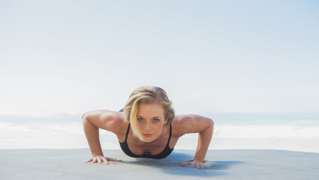 Fit blonde in plank position on the beach on a sunny day photo