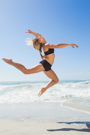 gracefully: Fit blonde jumping gracefully on the beach on a sunny day