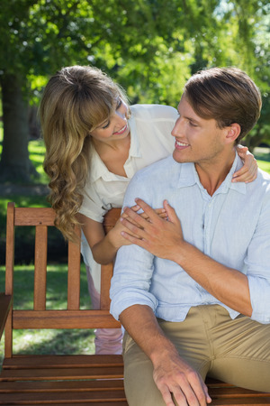 Affectionate couple relaxing on park bench together on a sunny day photo