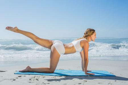 all weather: Gorgeous fit blonde in pilates pose on the beach on a sunny day Stock Photo