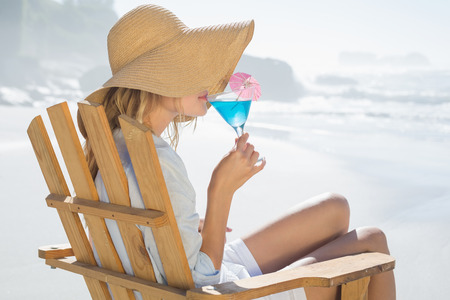 Smiling blonde relaxing in deck chair by the sea sipping cocktail on a sunny day photo
