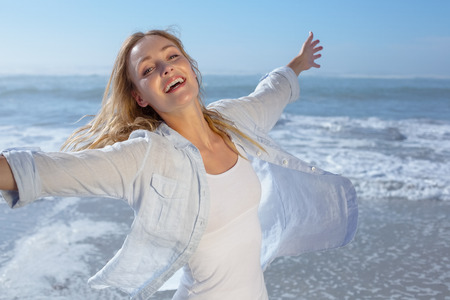 escapism: Gorgeous blonde spreading arms out at the beach on a sunny day Stock Photo